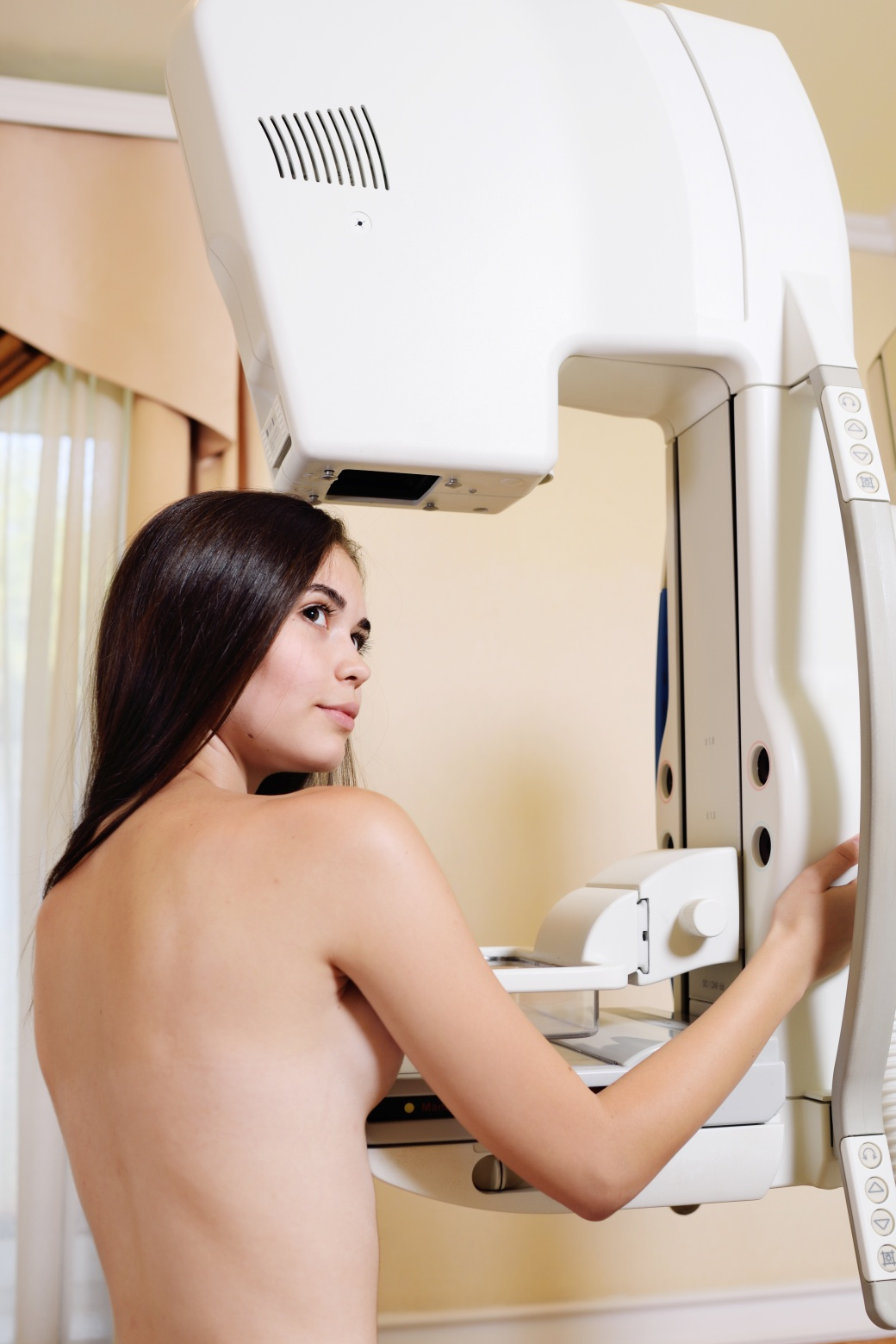 cute young girl on the examination of the breast using the mammography x ray machine, which carry out examination of the breast .